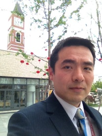 Dr Chen in front of the College's iconic bell tower